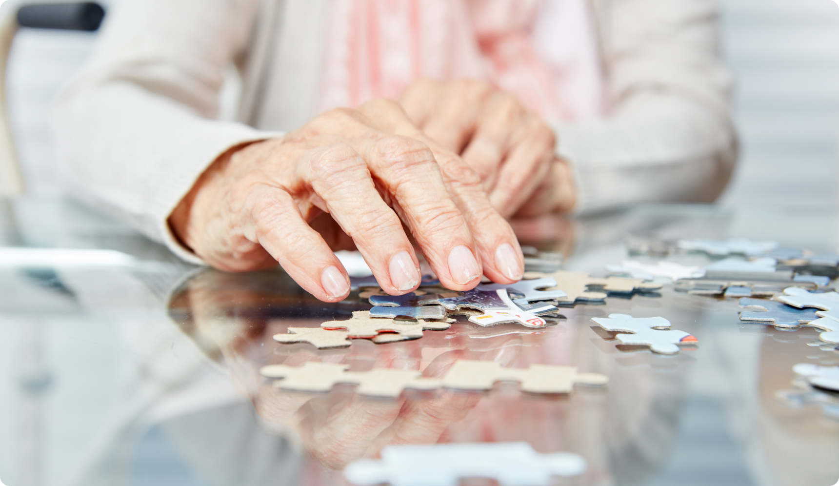 Elderly hands over puzzle pieces