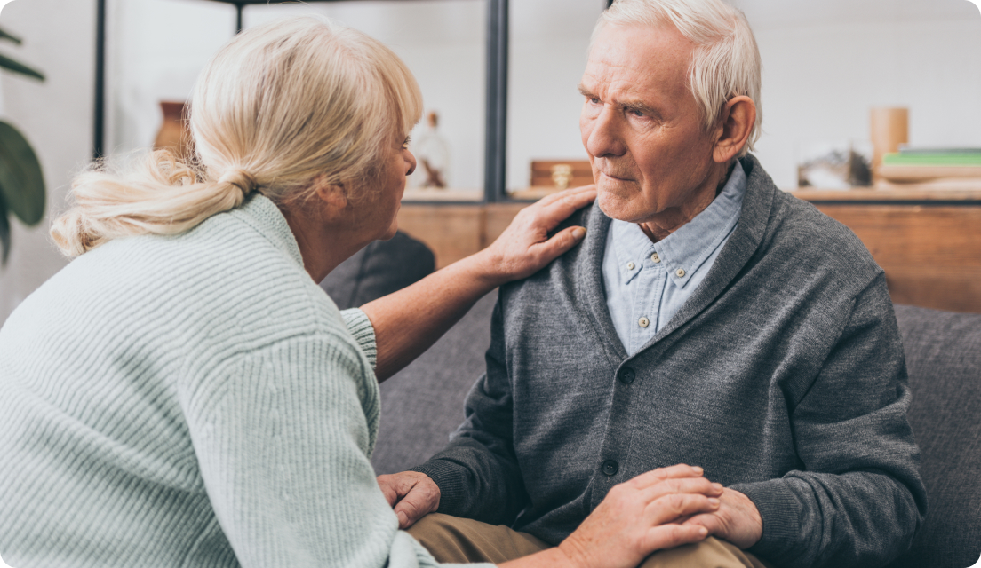 Senior man looking confused while wife comforts him