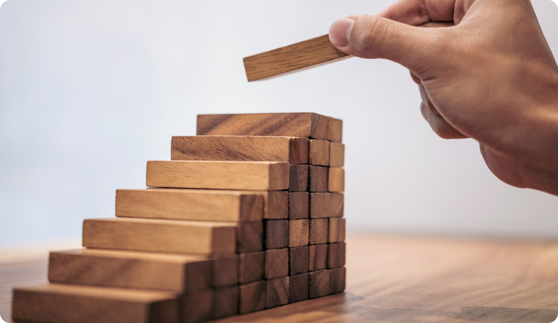Persons hand seen stacking up wooden blocks