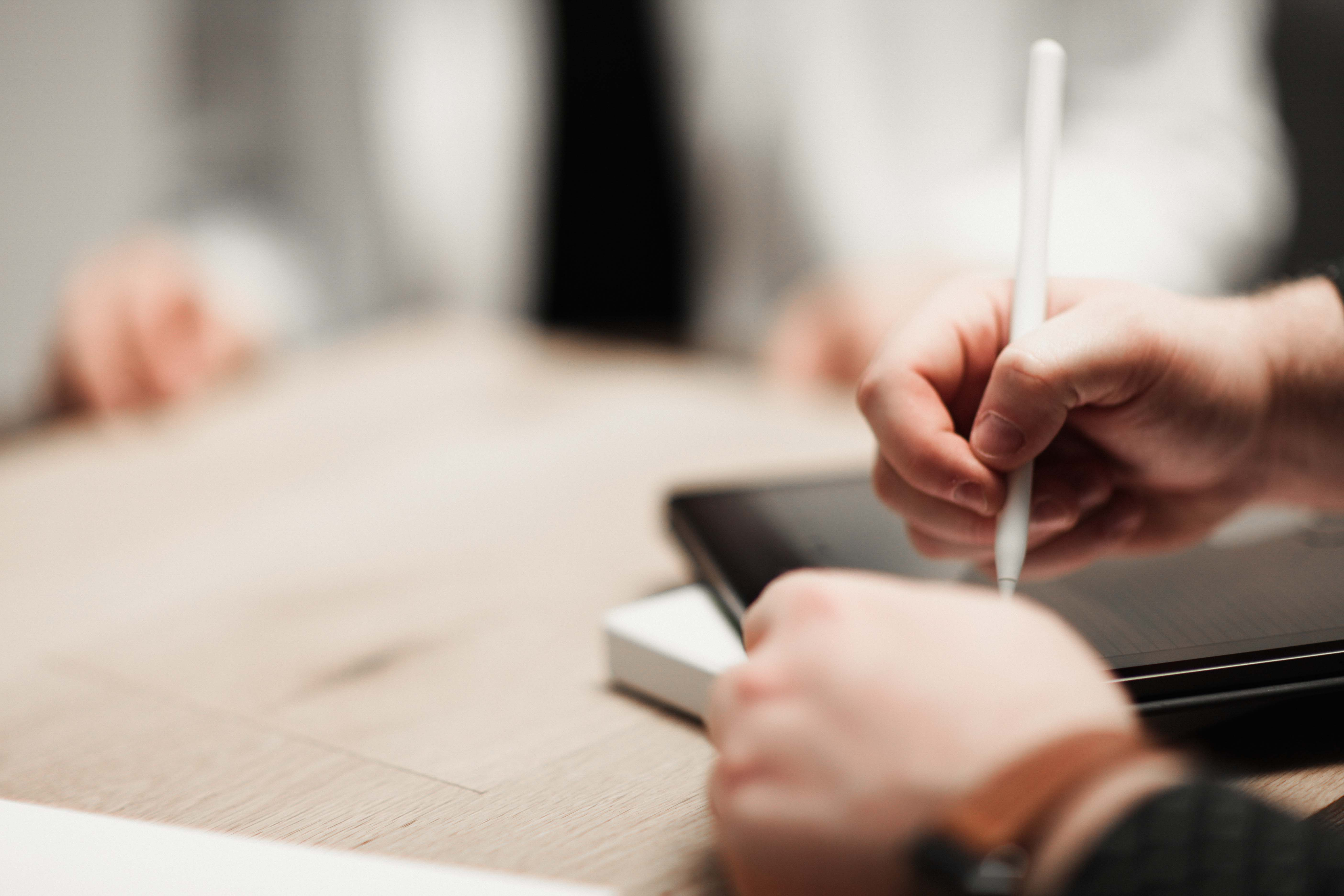 Close-up of person using a stylus to write on an iPad