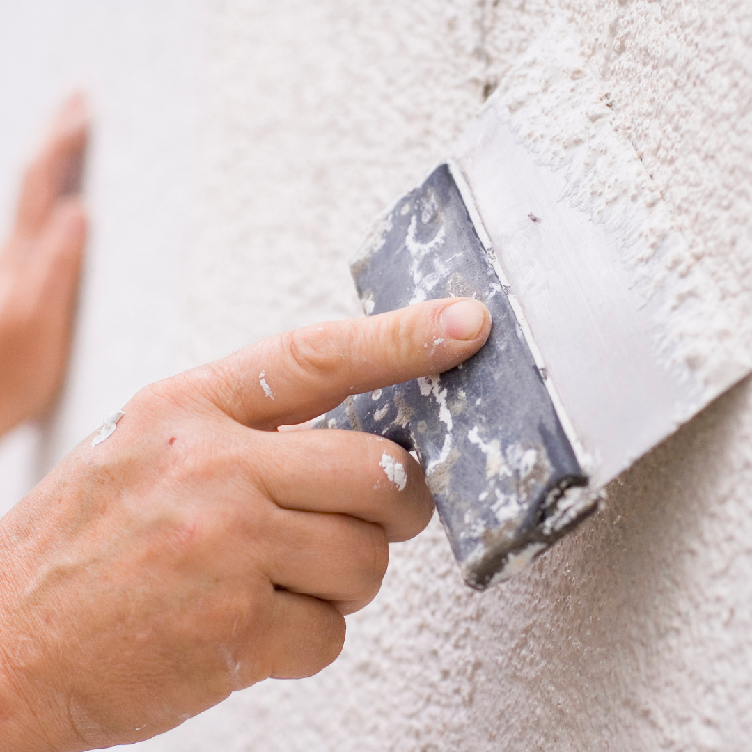 Person applying plaster to a wall