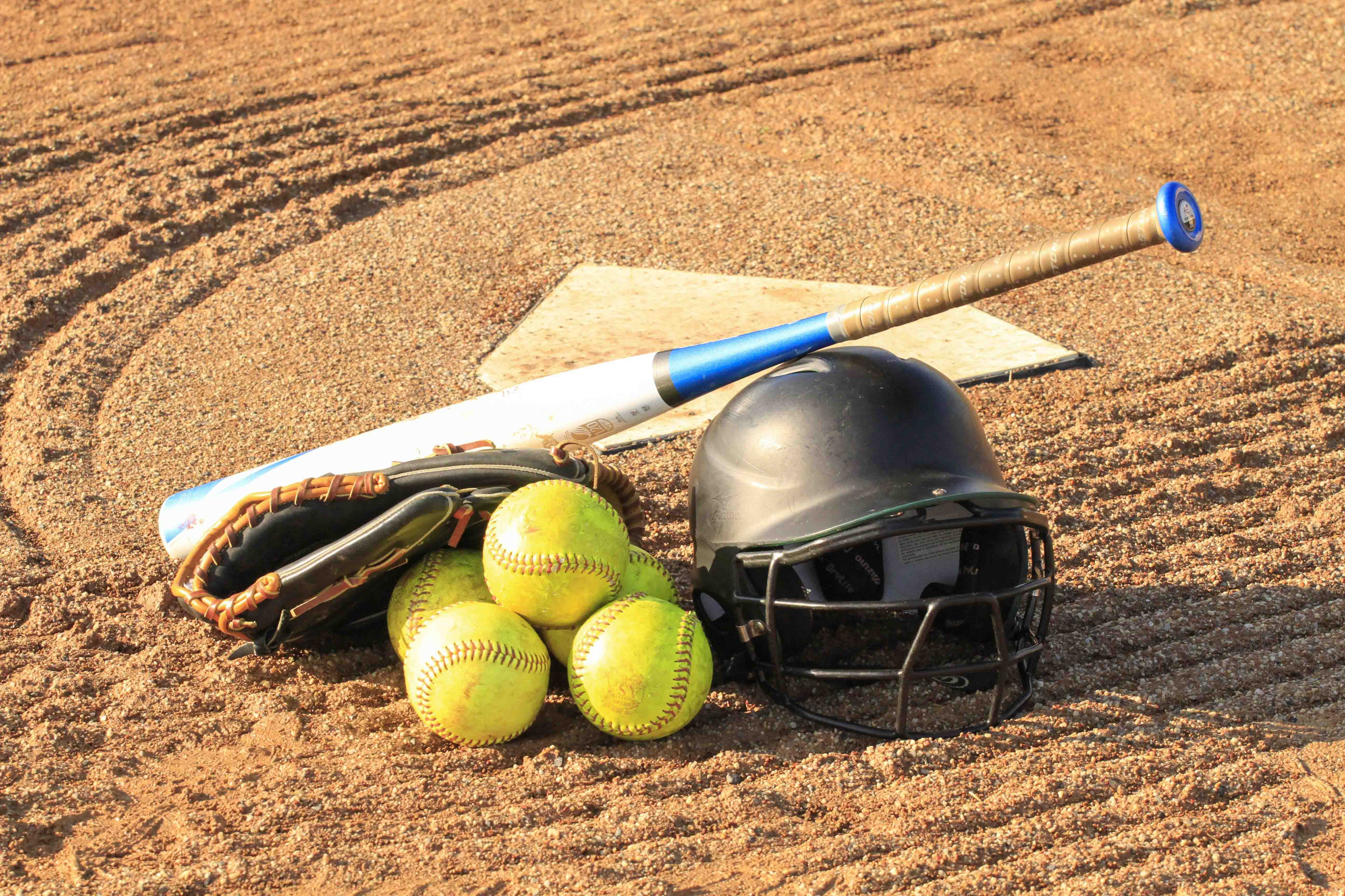 Softballs, a bat, and a helmet laying on the field