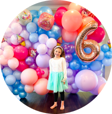 A girl standing in front of a balloon backdrop