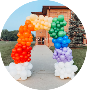 A rainbow balloon arch with clouds at the bottom