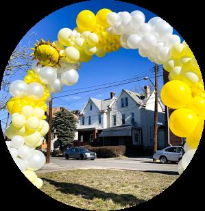 A yellow balloon arch with a sunshine mylar balloon