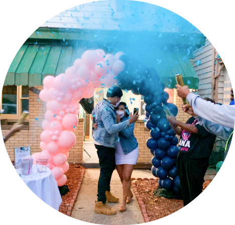 A couple hugging underneath a black and pink balloon garland