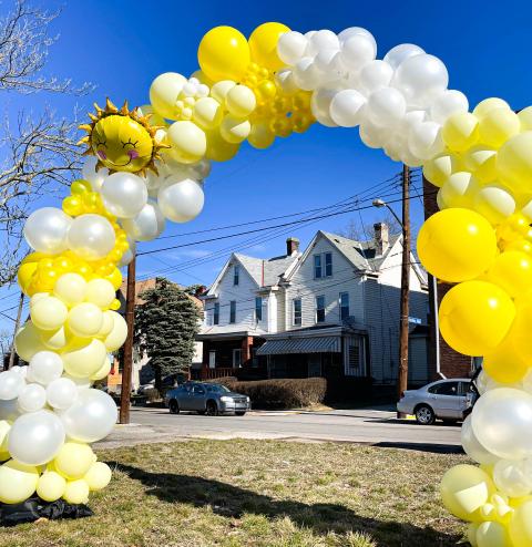 A yellow balloon arch with a sunshine mylar baloon