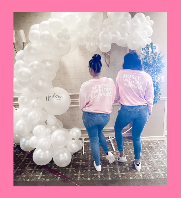 Two women standing in front of a white balloon garland