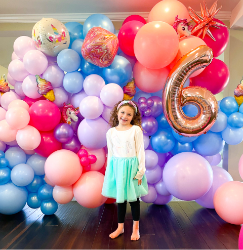 A girl standing in front of a balloon wall