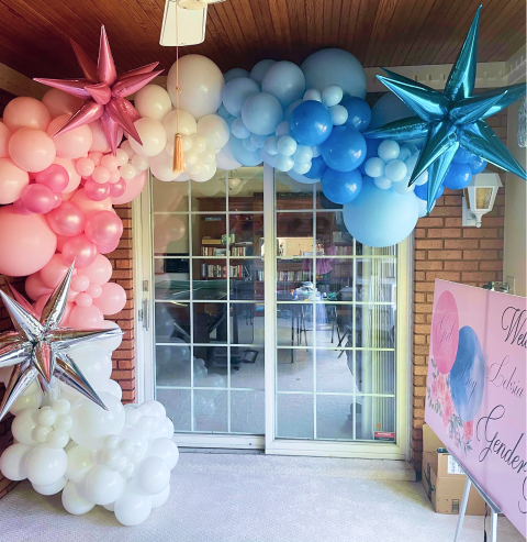 A blue, pink, and white colored balloon garland