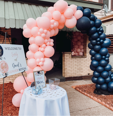 A pink and black balloon arch