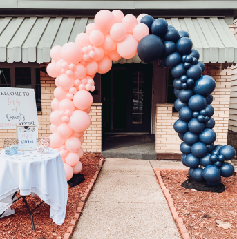 A black and pink balloon arch