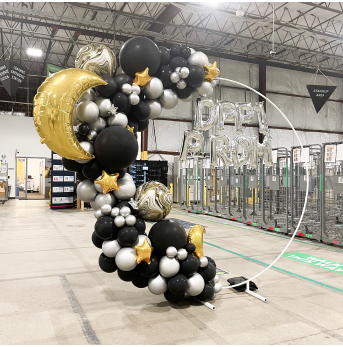 Black, silver, and gold balloons in a circle backdrop