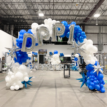A blue and white balloon arch with silver letters