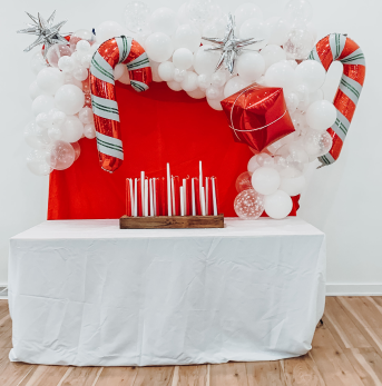 A holiday balloon background with white balloons and candy canes