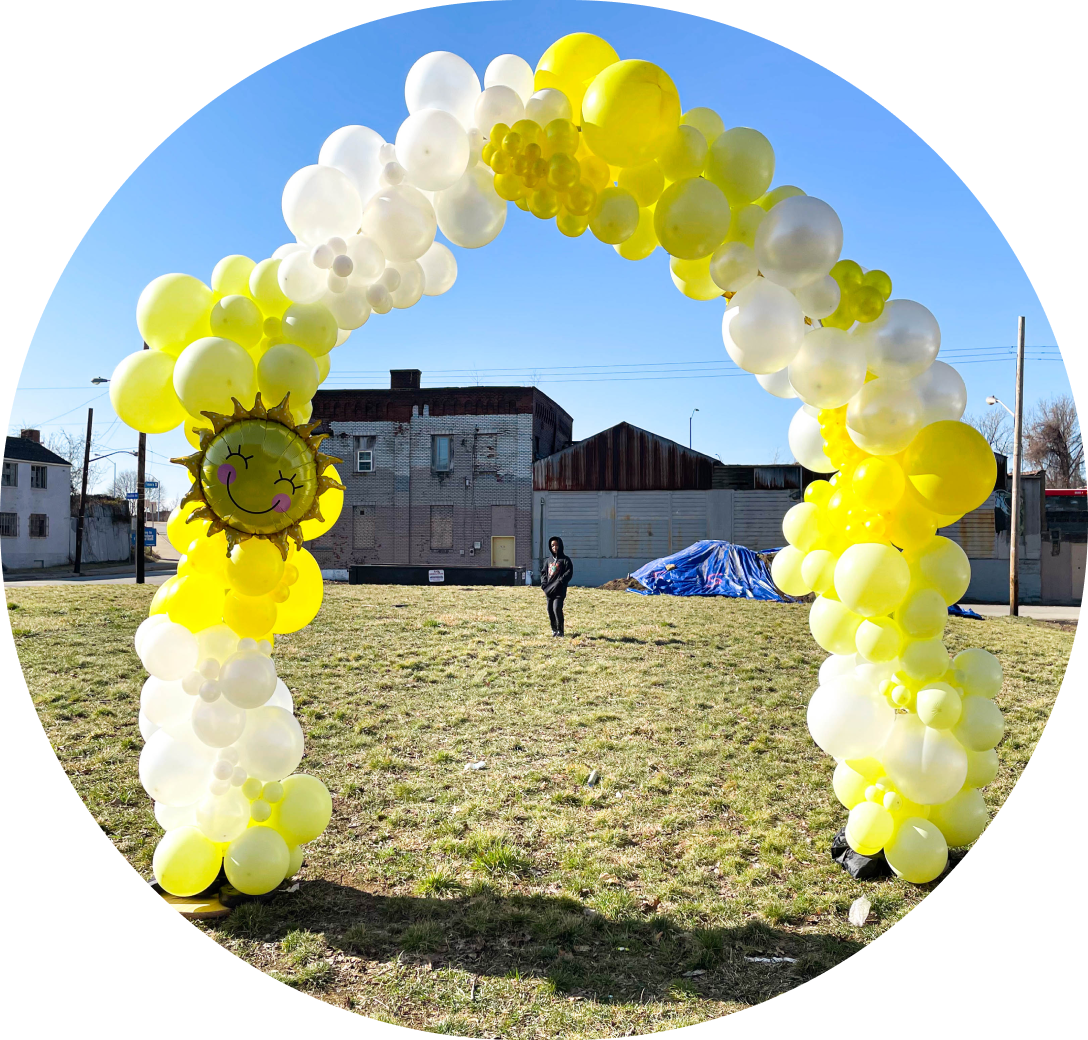 A yellow and white balloon arch