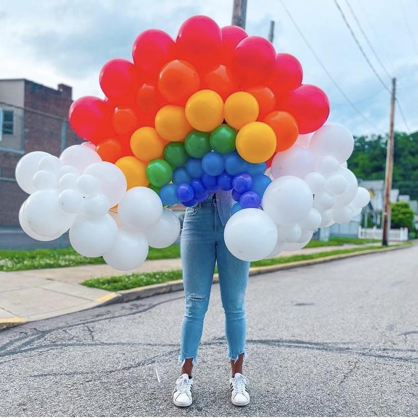 A woman holding up a rainbow made out of balloons