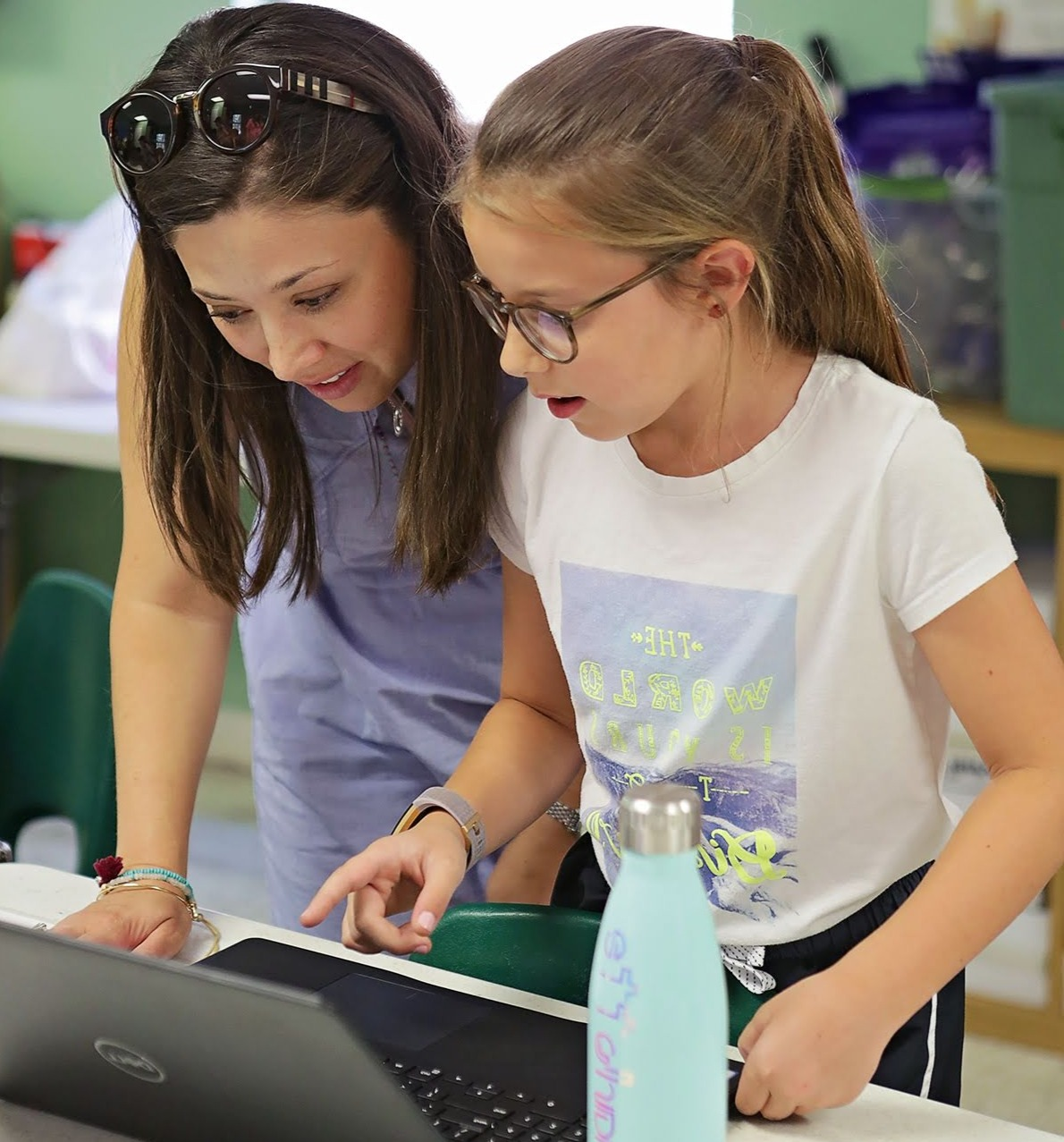 Instructor and young girl problem solving on a laptop computer.