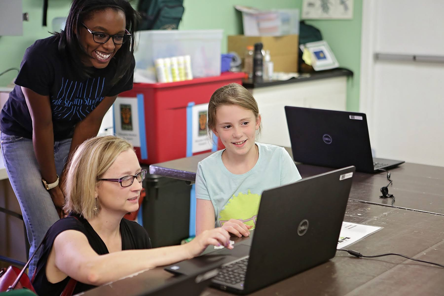 CodeStream Instructors and young girl, smiling at a laptop computer.