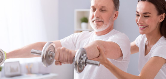mężczyzna ćwiczy razem z rehabilitantką