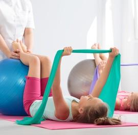 dziewczynka ćwiczy przy pomocy piłki z rehabilitantką
