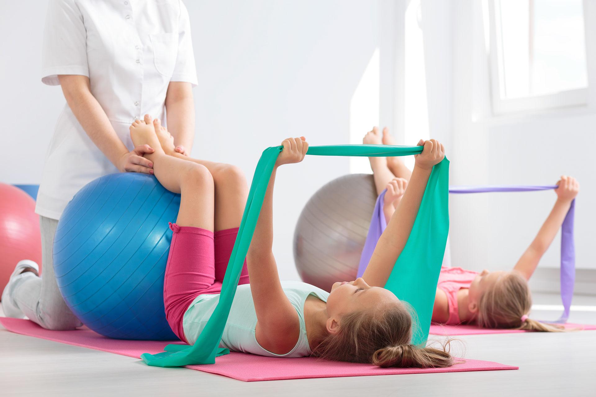 fizjoterapia dziecięca dziewczynka ćwiczy przy pomocy piłki z rehabilitantką