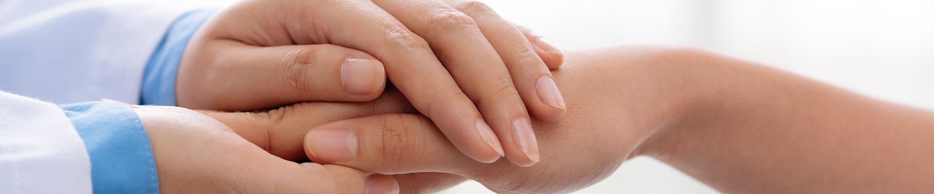 dłonie lekarza trzymające dłonie pacjenta