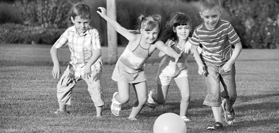dzieci  w parku biegnące za piłką