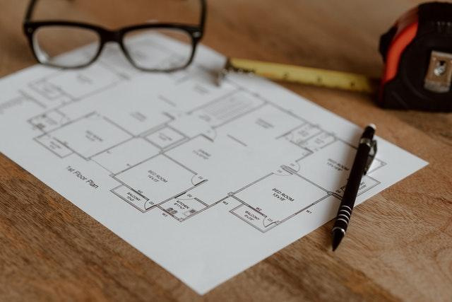 Planritning på ett bord med en penna och ett par glasögon närvarande
