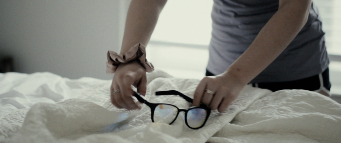 A person picking up the lumos glasses from the bed