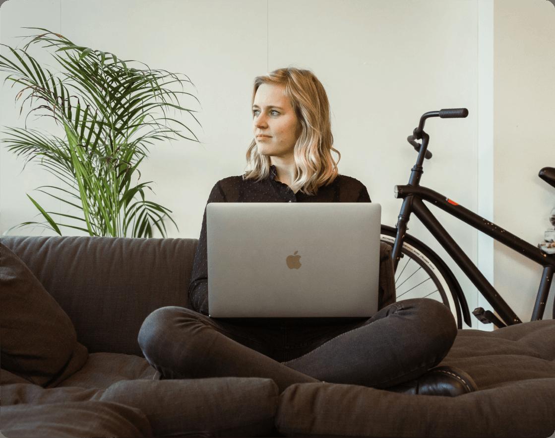 Remote werkende dame die op een bank zit met een laptop op haar schoot