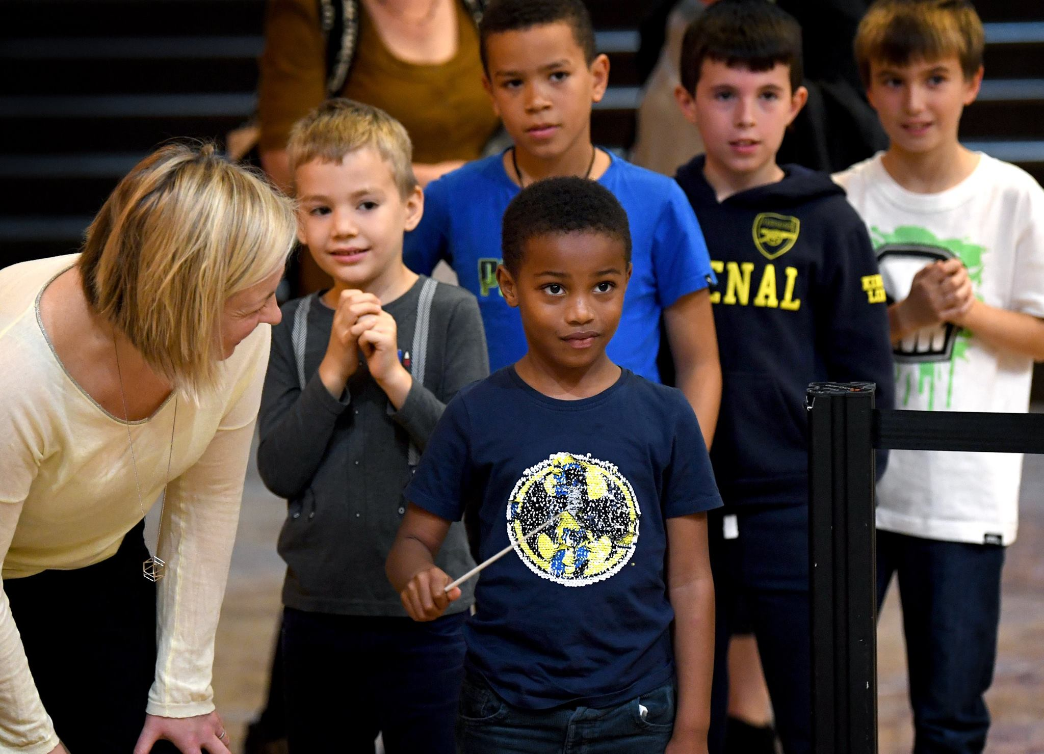 A small British boy of African descent wearing a blue teeshirt with a yellow superhero logo on the front holds a conducting baton and looks towards the photographer. Behind him are four more boys, slightly older than him, waiting for their turn. On the left of the photo is a blonde, white woman, bending own and smiling at him in encouragement.