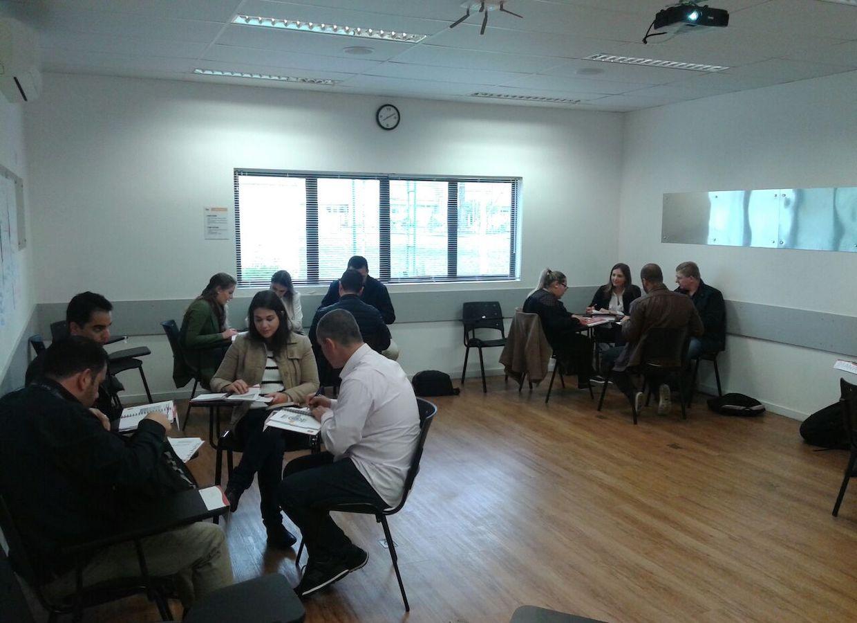 sala de treinamento com grupos em mesas