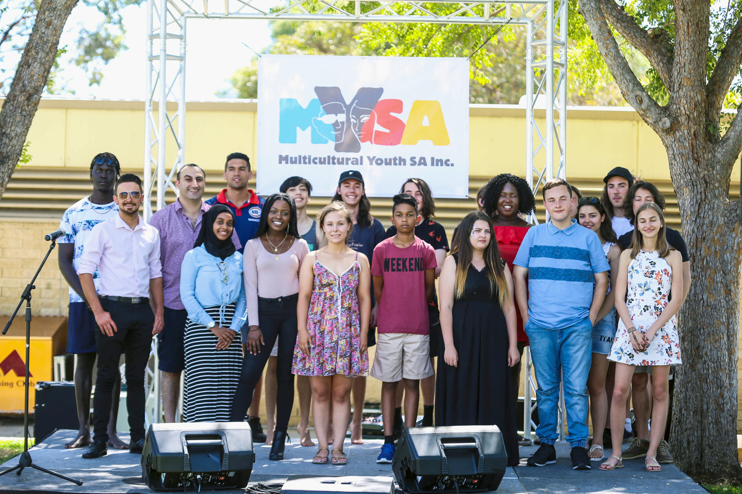 Young adults stand together in from of a MYSA banner.
