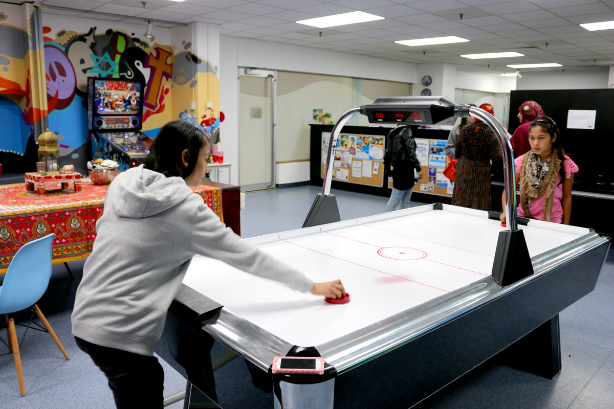 Kids play air hockey at The Hub.