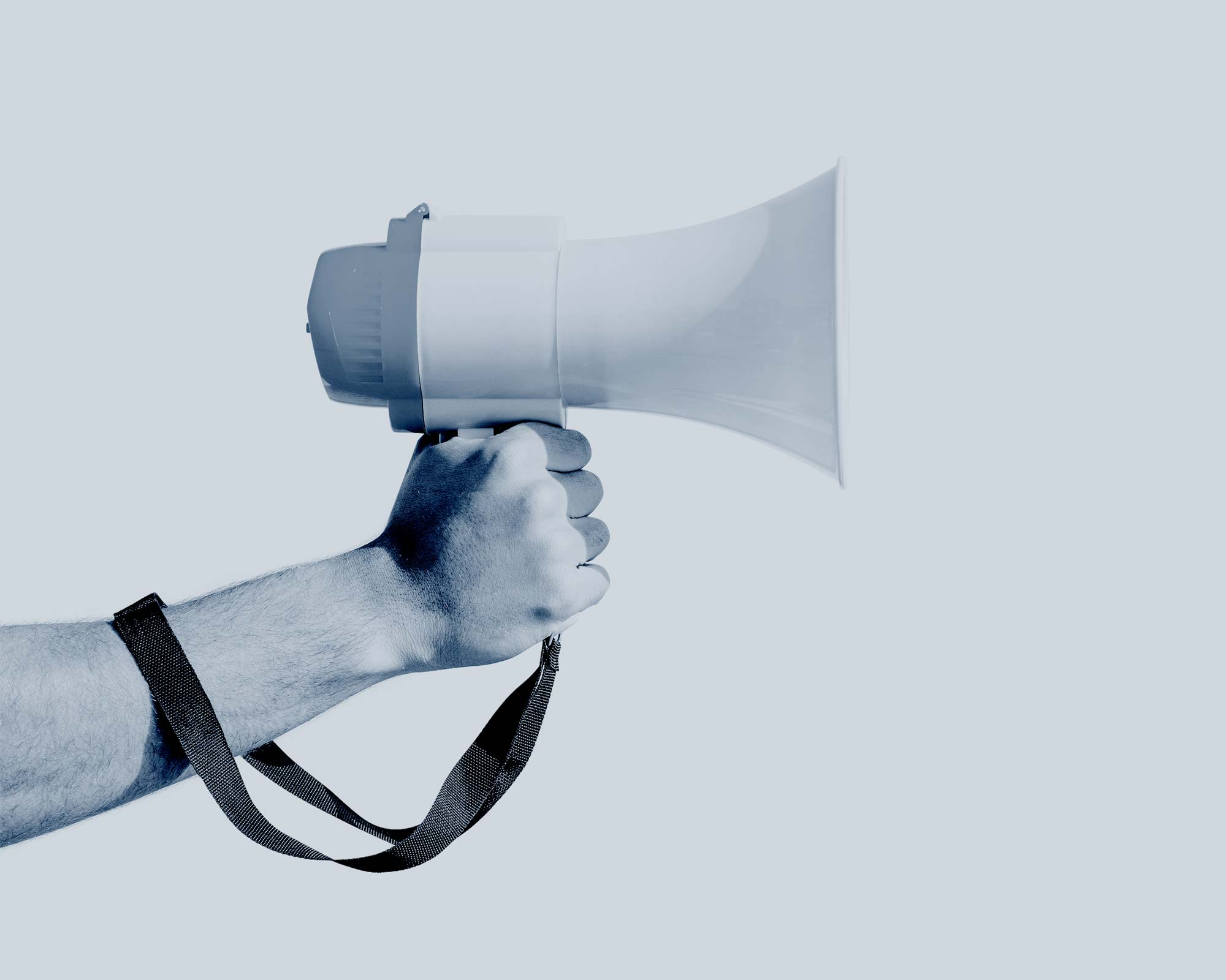 A hand holding a megaphone with the strap wrapped around the wrist.