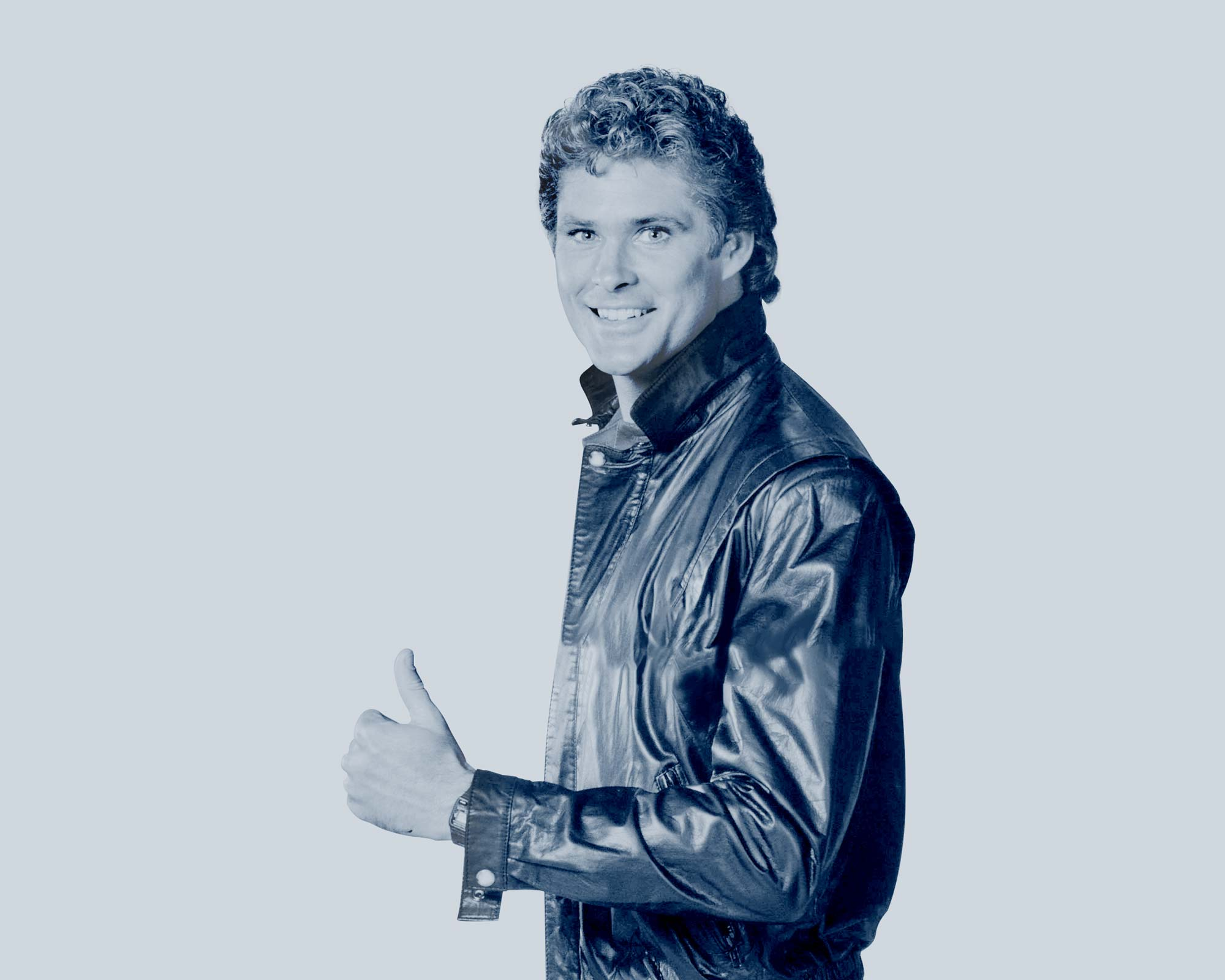 A picture of David Hasselhoff in a leather jacket smiling and looking at the camera with his thumbs up.