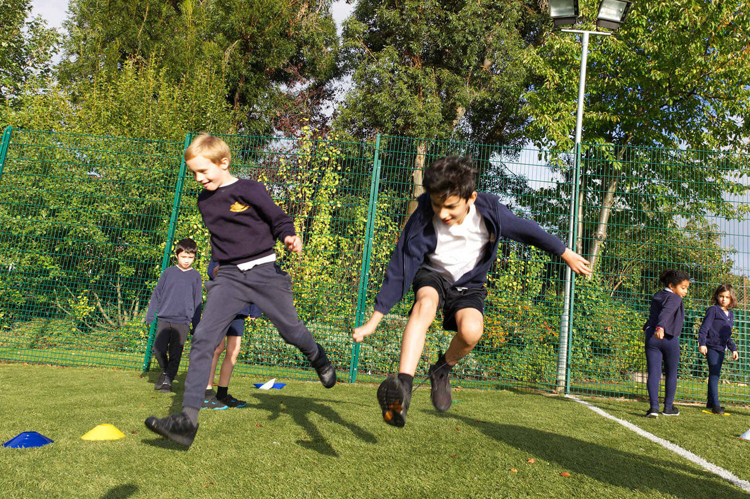 School boys in PE lesson jumping in air on the astro turf