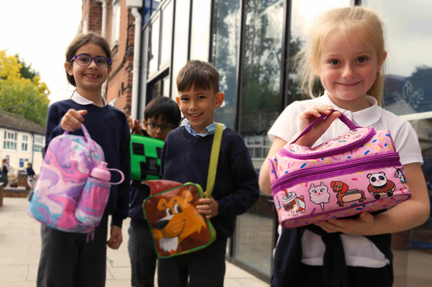 Children at school holding their lunchboxes