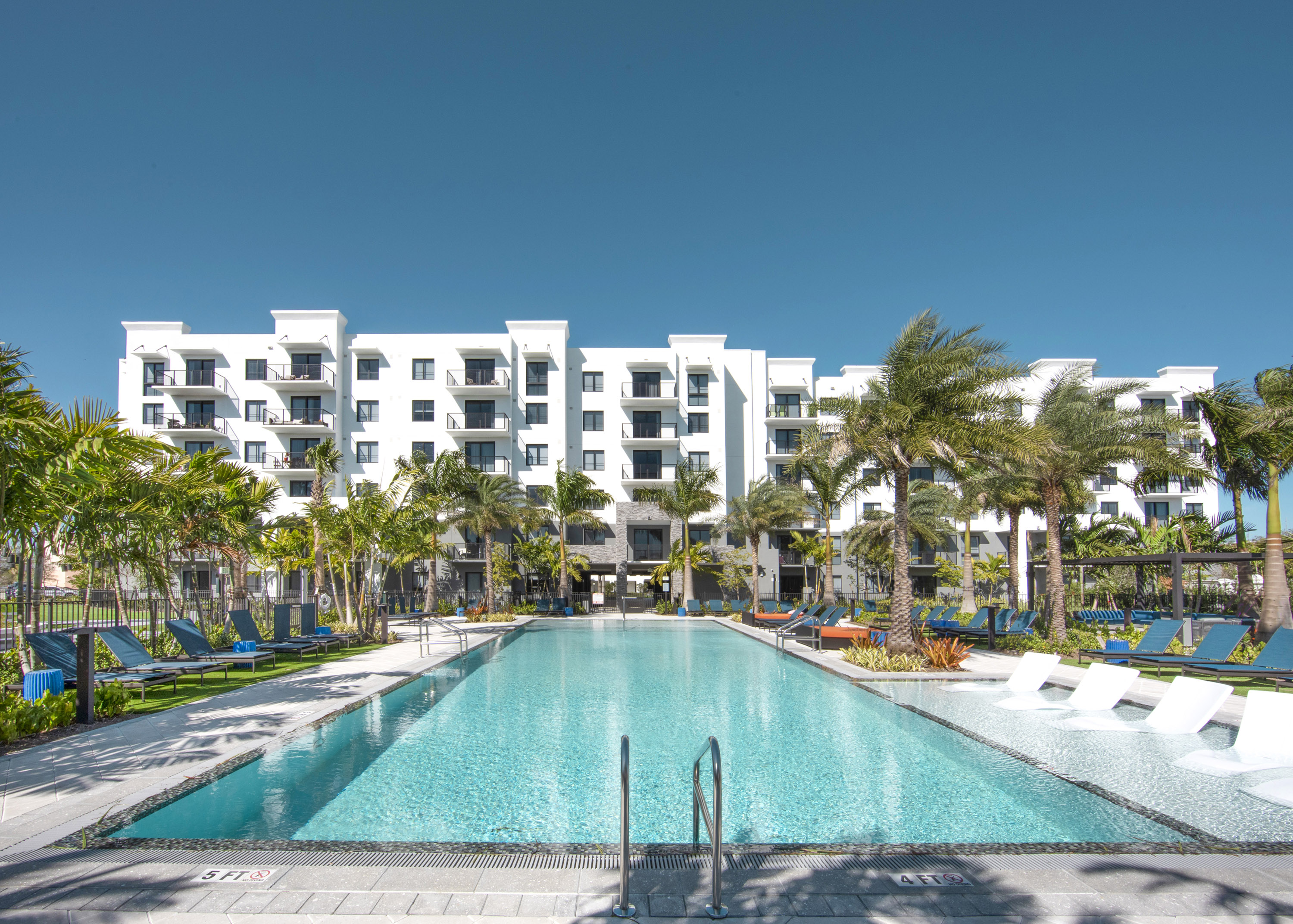 sanctuary pool surrounded by palm trees and Sanctuary Doral apartments behind