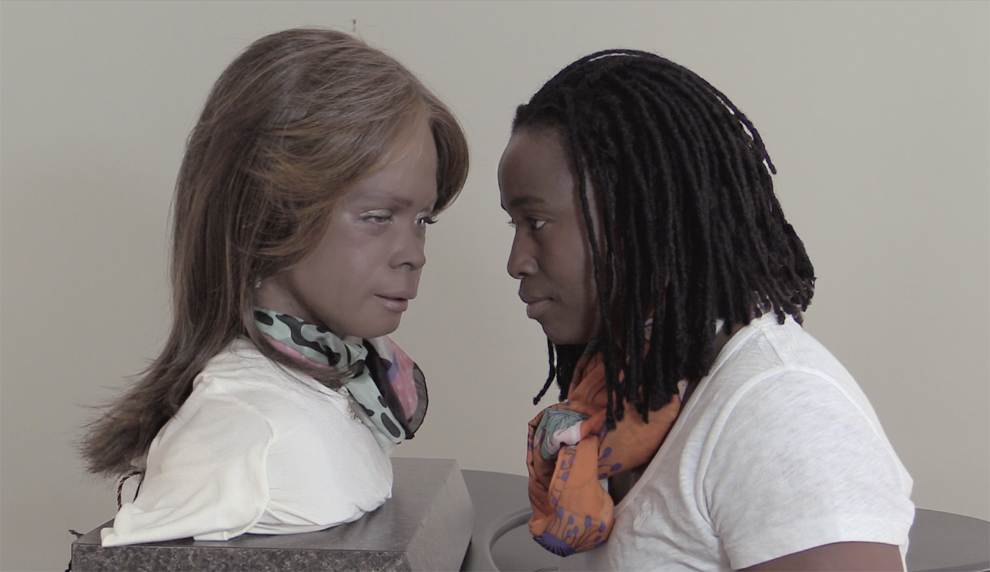 """Seen in profile, the artist, a Black woman with dark brown skin, stares at Bina48, a robotic bust with medium brown-gray Frubber """"skin"""" and feathered brown shoulder length hair. The two subjects resemble each other, and they wear similar white t-shirts and scarves. Their heads are close in proximity."""