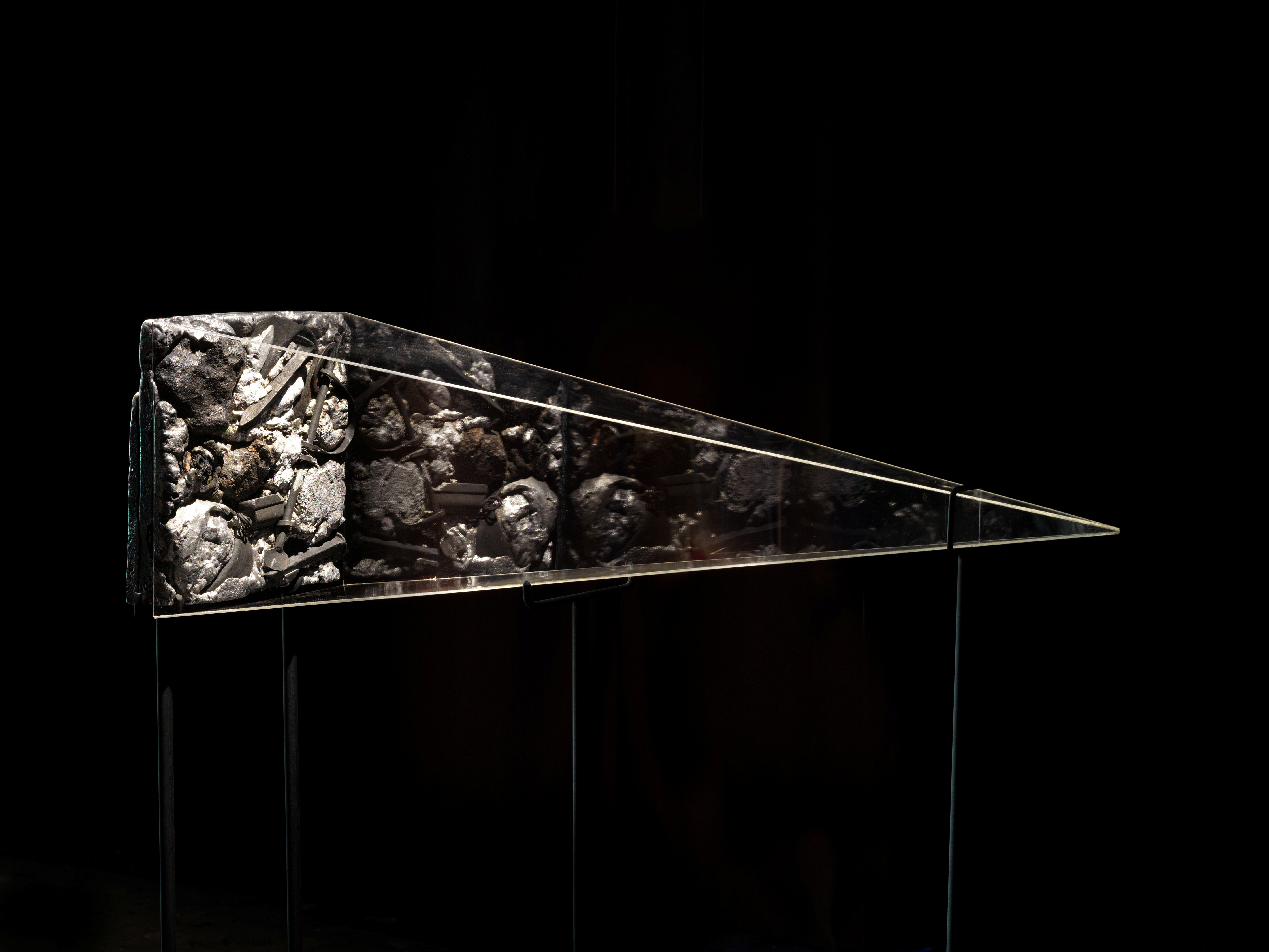 A pyramid vitrine lays on its side shrouded in darkness. Inside the vitrine is an illuminated collage of railroad nails, shackles, and various metals.