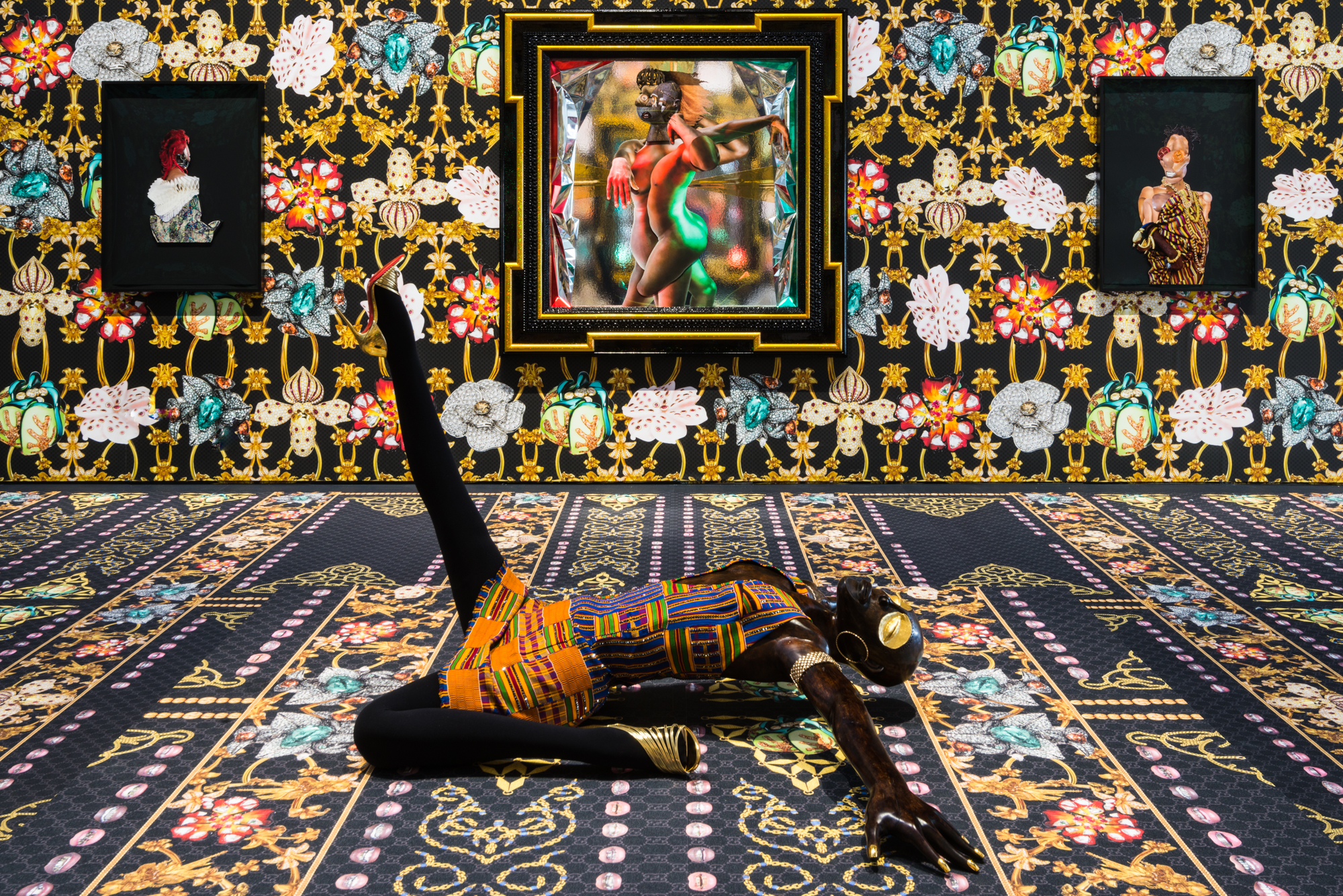A sculpture of a Black woman lays on the floor, one leg straight up in the air, the other bent back at her side. Her arms are fanned out, head bent back, gold disc eyes closed. In the background, there are three portraits depicting various figures. The floor, walls, and clothing are a cacophony of floral and geometric patterns.