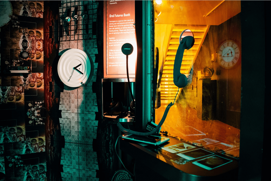 """A view from the interior of a dimly lit booth bathed in a teal glow. A clock, a telephone, a shelf holding various tablets and photographs, and a plaque identifying the structure as the """"Oral Futures Booth"""" adorn the wallpapered structure. The rest of the amber-colored gallery can be seen through a window in the booth."""