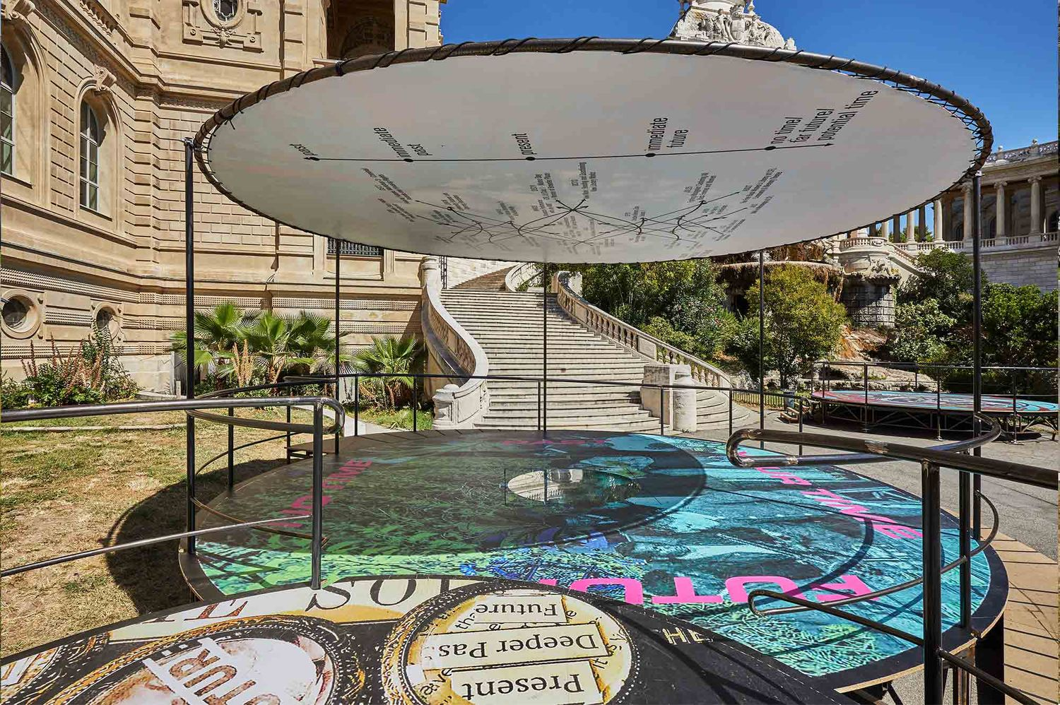 Outside the Palais Longchamp there is a cylindric stage interlocking with another cylindric stage. Both of the circular platforms have graphic text and digital textures patterning the floor.