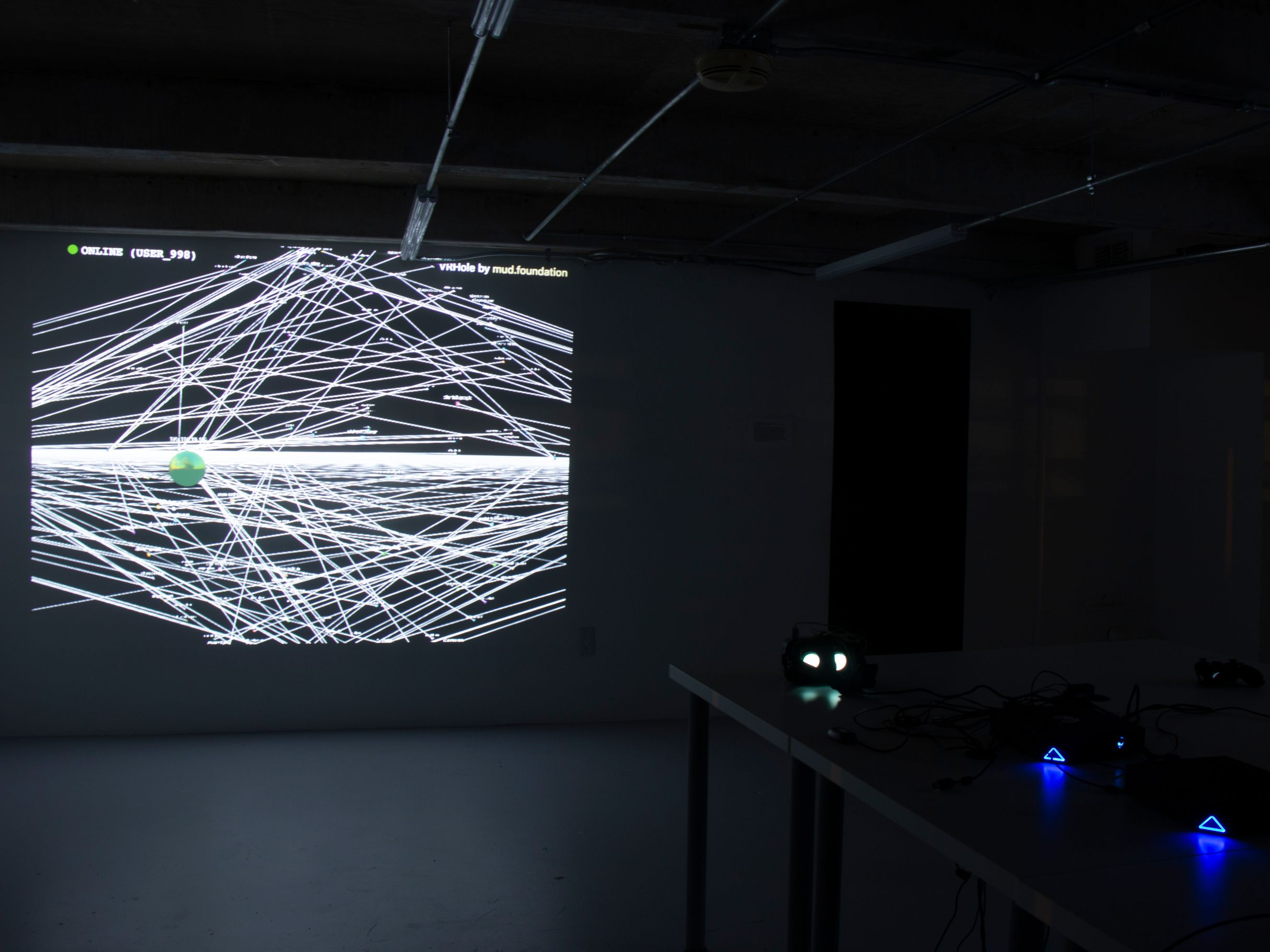 A dark rectangular room illuminated by a projection of intersecting white lines. A table to the right of the projection has VR glasses that glow white and blue.
