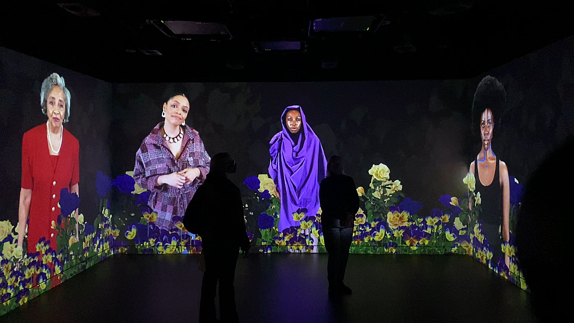 A large projection covers three walls of a dark room, showing a video of four Black women of various ages standing in a digitally collaged field of purple and yellow flowers. Two silhouettes are just barely visible, standing in the middle of the room and watching the video.