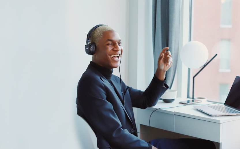 Person with headphones, in a conversation, smiling