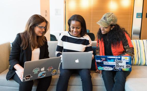 Three people huddling on their laptops