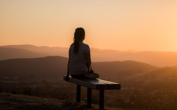 Person sitting on a bench outdoors and watching the sun rise